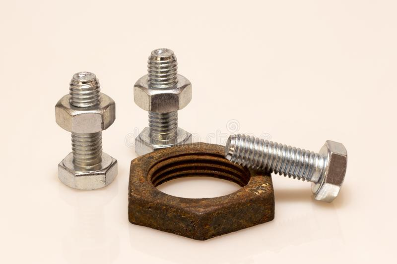 New bolts with nuts and old rusty nut royalty free stock photography