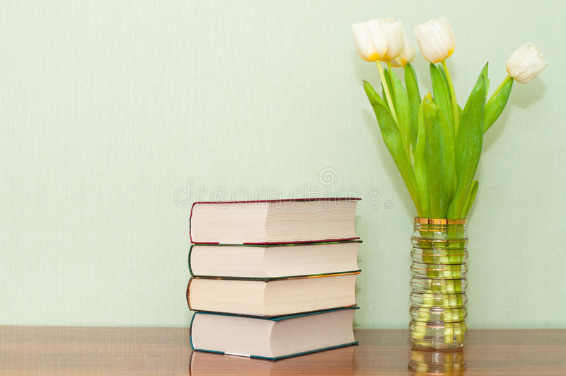 New books with a bouquet of tulips on a wooden table royalty free stock photo