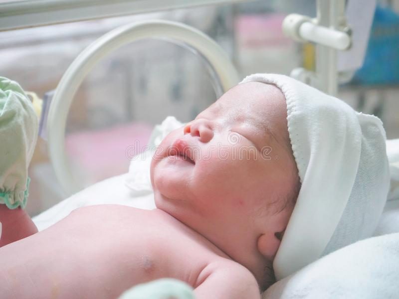 New born baby infant sleep in the incubator at hospital. New born baby infant girl sleep in the incubator at hospital royalty free stock image