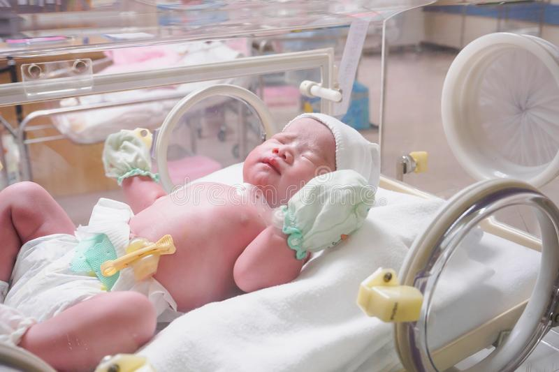 New born baby infant sleep in the incubator at hospital. Post delivery room stock images