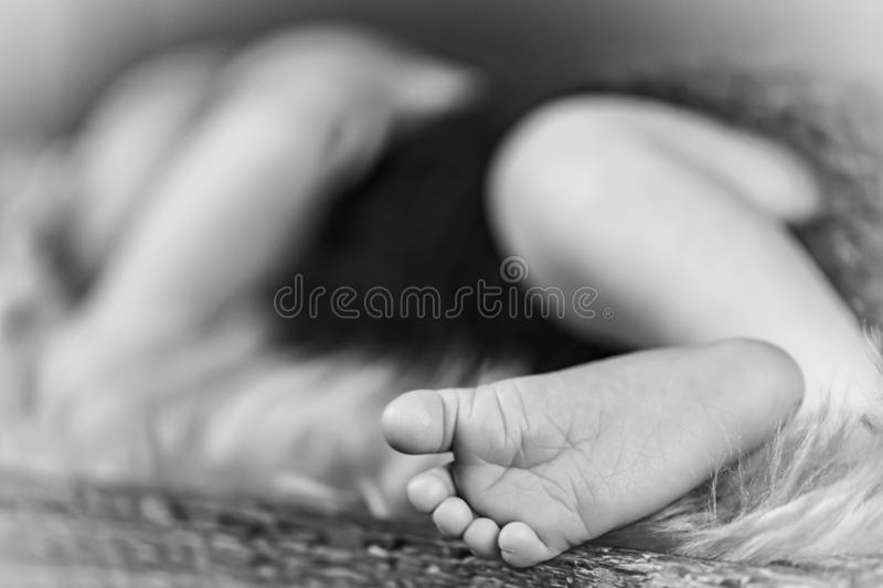 New born baby`s foot, sleeping baby in the background - black and white stock photos
