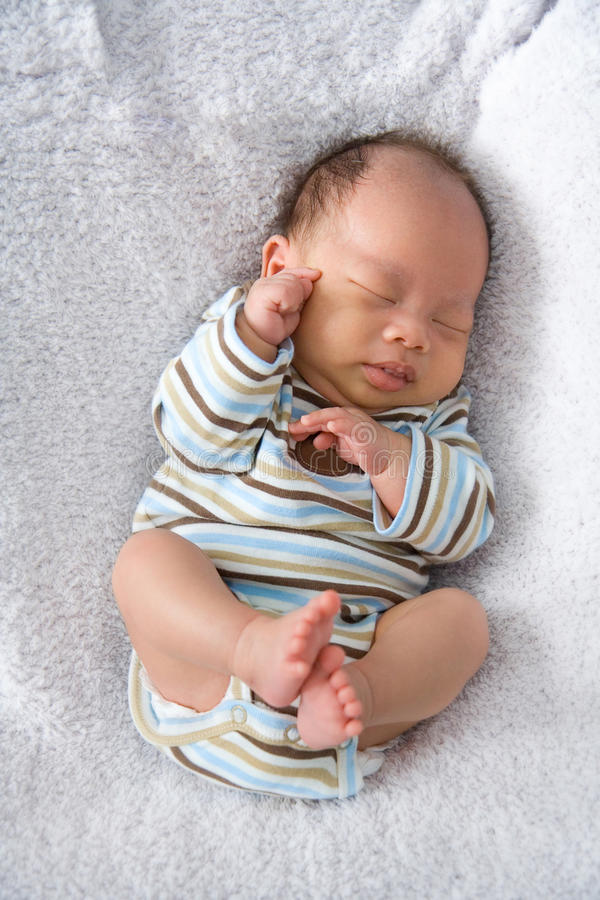 New Born Baby sleeping. On a white furry blanket royalty free stock photography