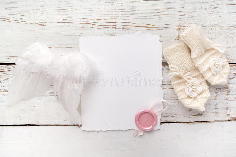 New Born or baptism Greeting Card. Blank with baby girl gloves and angel wings on white wooden background stock photos