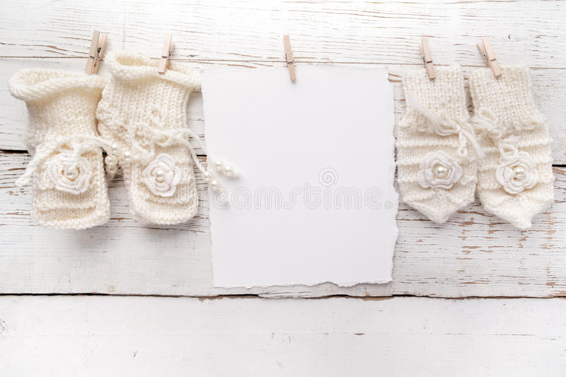 New Born or baptism Greeting Card. Blank with baby girl shoes and gloves on white wooden background stock photos