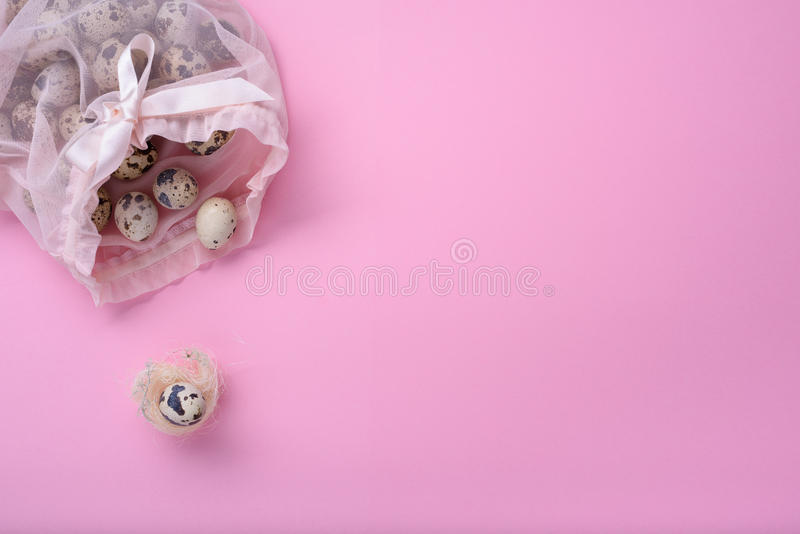 New born child, baby shower or pregnancy greeting card concept. Quail egg in a birds nest over pink background stock image