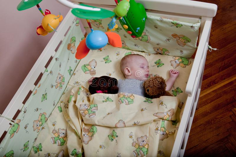 New born child in wooden co-sleeper crib. Infant sleeping in bedside bassinet. Safe co-sleeping in a bed side cot. Little boy taki. Ng a nap under knitted stock photography