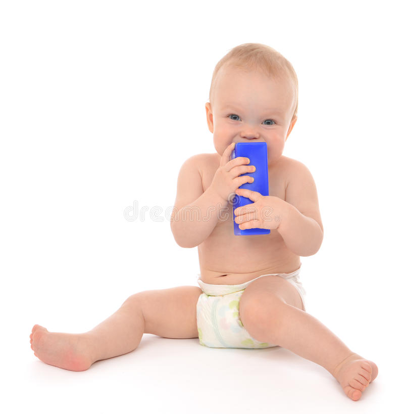 New born infant child eatind blue toy brick. New born infant child baby girl toddler sitting happy smiling eatind blue toy brick in hand on a white background stock images