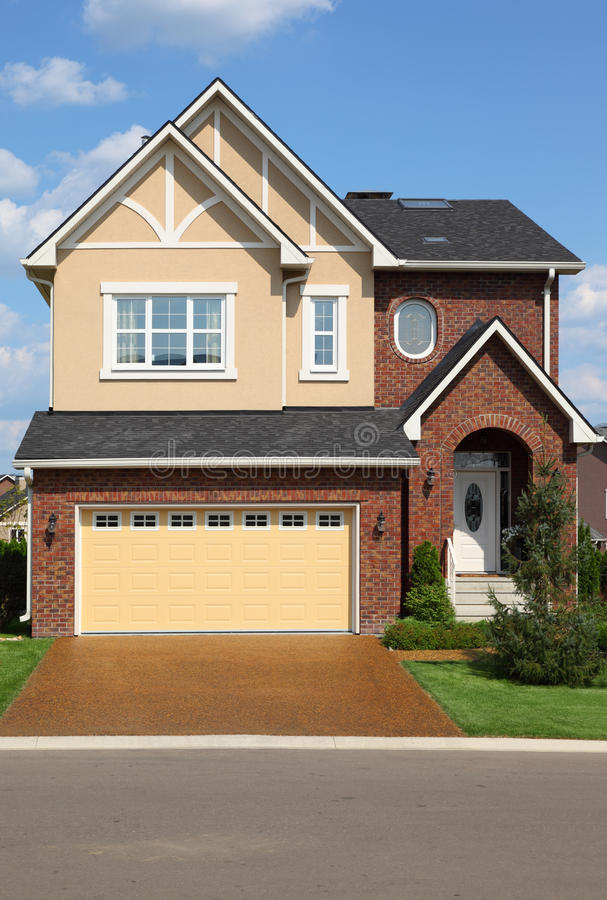 New brick cottage with garage on first floor stock photo for Brick garages prices