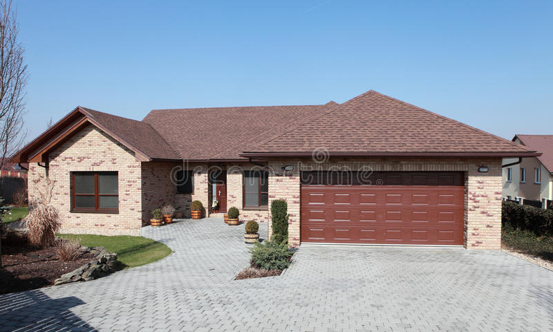 New brick house. Just finished modern brick house with large garage doors, roof tiles and pavement stock photo