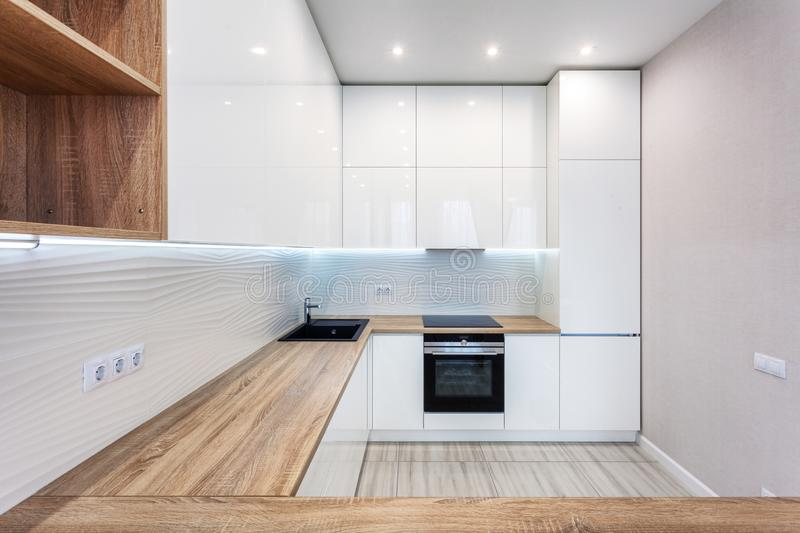 New bright modern kitchen with built in oven and chrome water tap and a wooden table top. New bright modern kitchen with built in oven and chrome water tap and stock photo