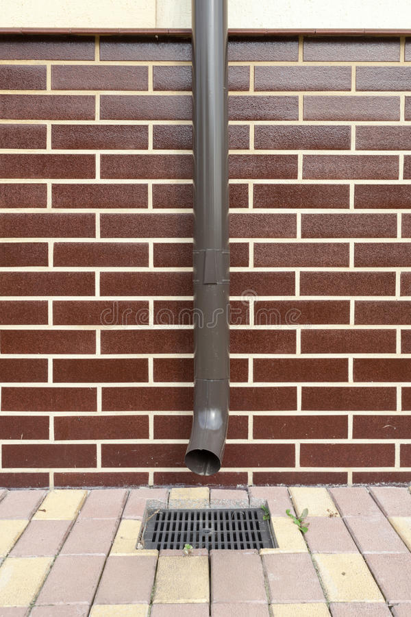 New brown copper drain in a house with brickwork. stock photography