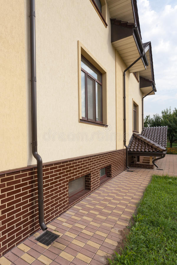 New brown copper gutter in house with white wall and new brick. Close up view on house problem areas for rain gutter. Guttering, gutters, plastic guttering royalty free stock photography