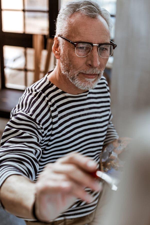Artist feeling inspired while working on new brushwork. New brushwork. Dark-eyed creative artist feeling inspired while working on new brushwork stock photography