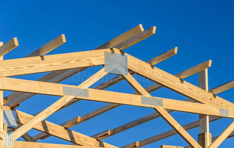 A new build roof with a wooden truss framework with a blue sky background. stock photo