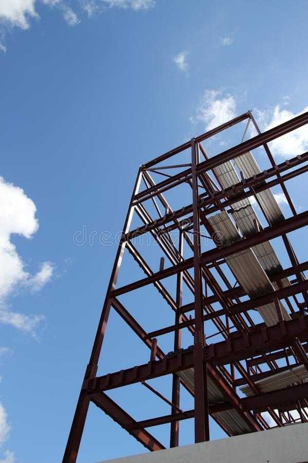 New building framework. A framework of a new building being built with a blue sky surrounding it stock photo