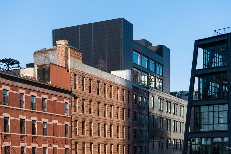 Old brick buildings contrasted with modern glass and steel architecture. New buildings contrasted with old buildings along The High Line in New York City royalty free stock photography