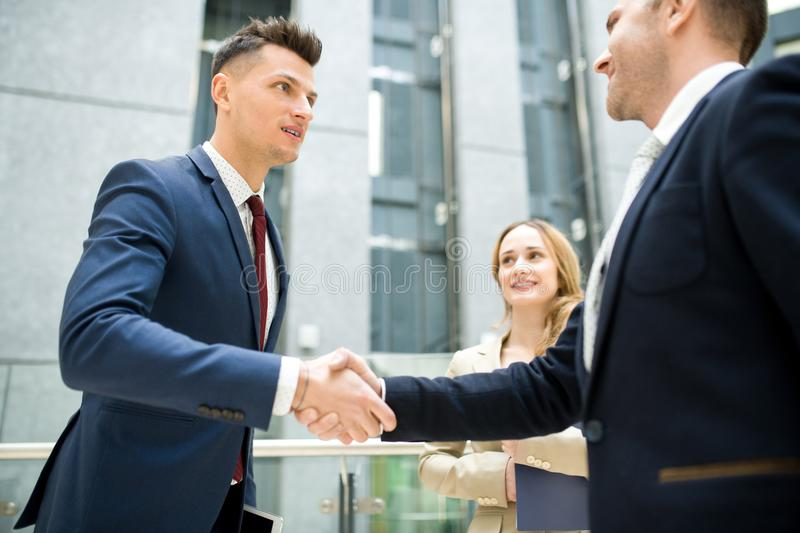 New business acquaintance. Content handsome young new business employee shaking hand of colleague while getting acquainted with team in office stock photo