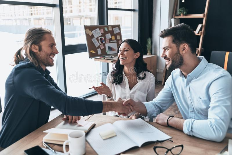 New business partners. Young modern colleagues in smart casual w. Ear shaking hands and smiling while sitting in the creative office royalty free stock photo