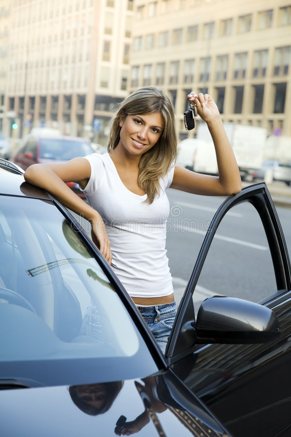 New car. Young woman holding keys to new car royalty free stock photography