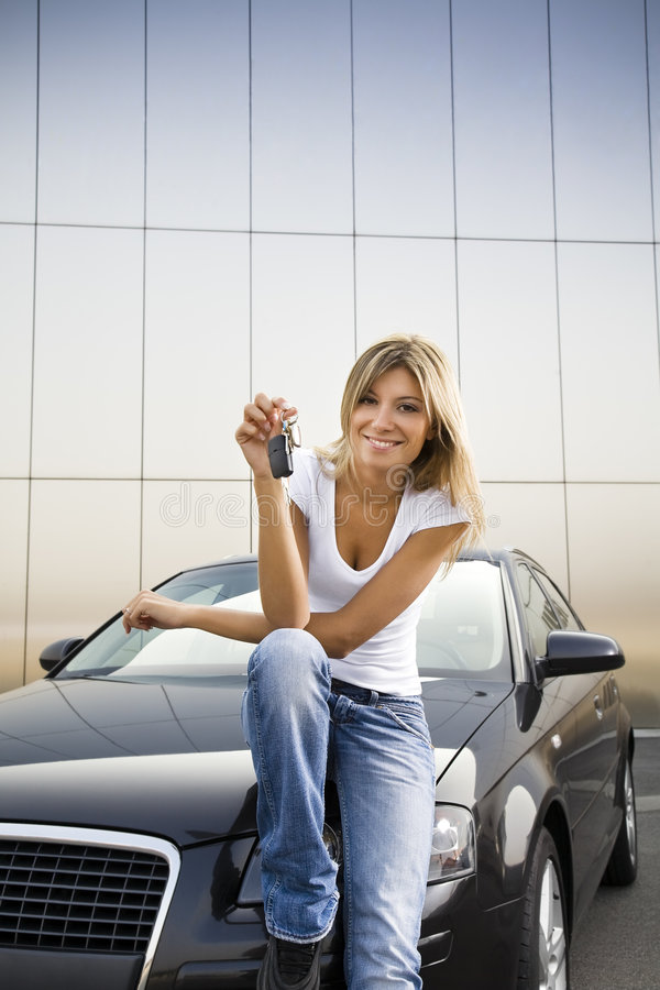 New car. Young woman holding keys to new car stock images