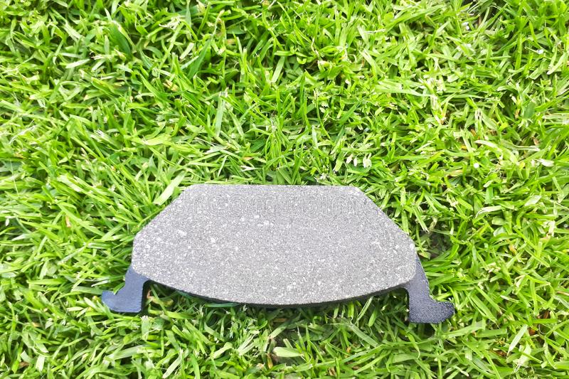 New car brake pad on green grass. Background stock photography