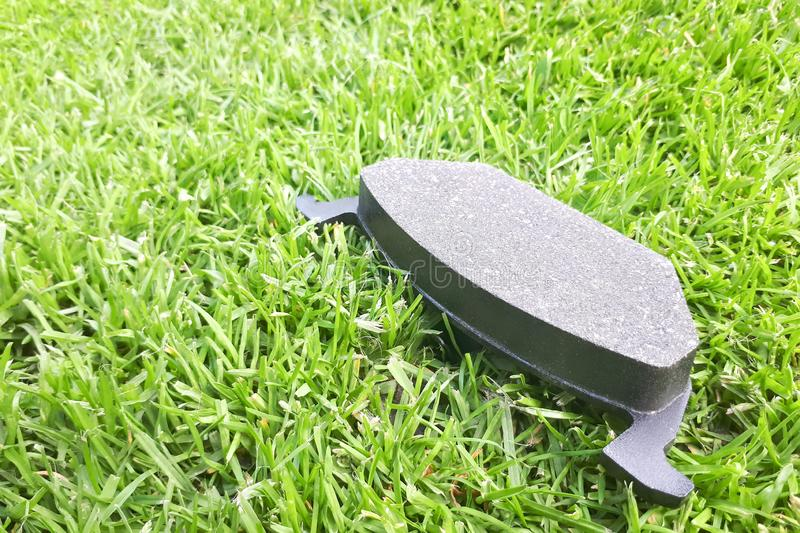 New car brake pad on green grass. Background stock photo