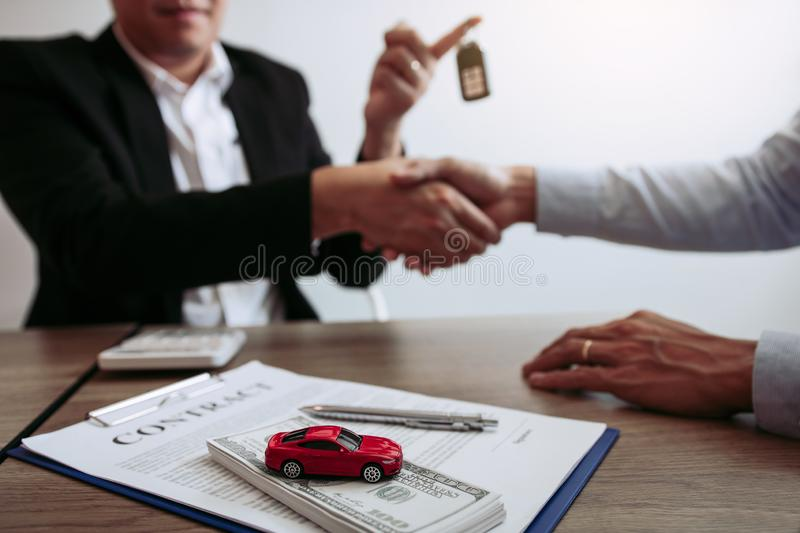 New car buyers and car salesmen are shaking hands to make agreements about car sales.  royalty free stock photos