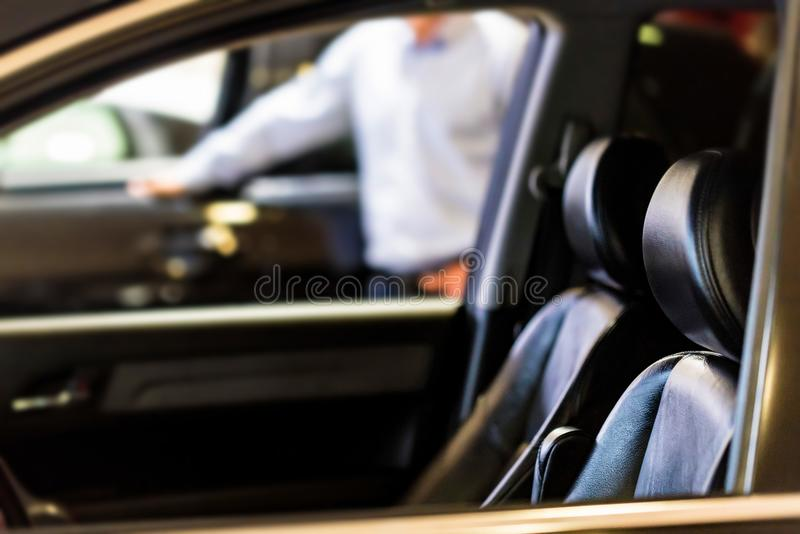 New car at dealer showroom blurred background. Close up of new car door and interior in showroom of automobile dealer with blurred background royalty free stock photography