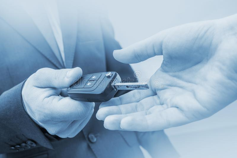 New Car Delivery Concept. Car Salesman Delivering New Vehicle. Giving New Car Keys. Blue Color Grading royalty free stock photo