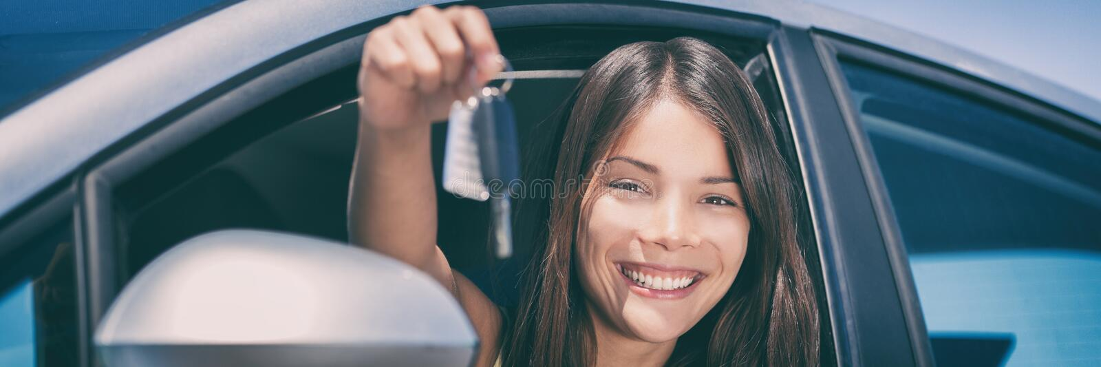 New Car driver young Asian woman driving automatic drive smiling showing new car keys panorama royalty free stock image