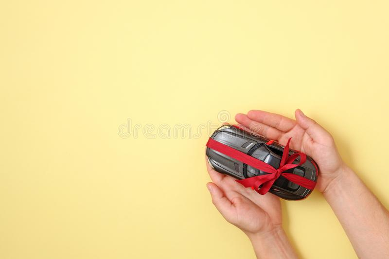 New car gift concept, Toy car with red ribbon in human hands on yellow background. Top view. Auto dealership and rental, raffle stock photos