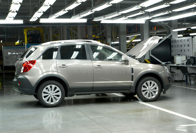 The new car with an open cowl costs in assembly shop. Automobile. Plant stock photo