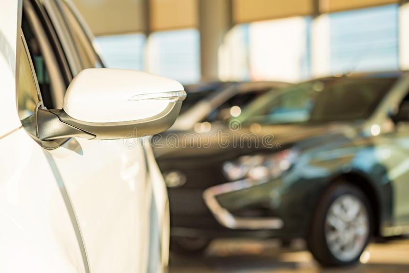 New cars at dealer showroom blurred background. Stock of cars in showroom of automobile dealer with blurred background royalty free stock images