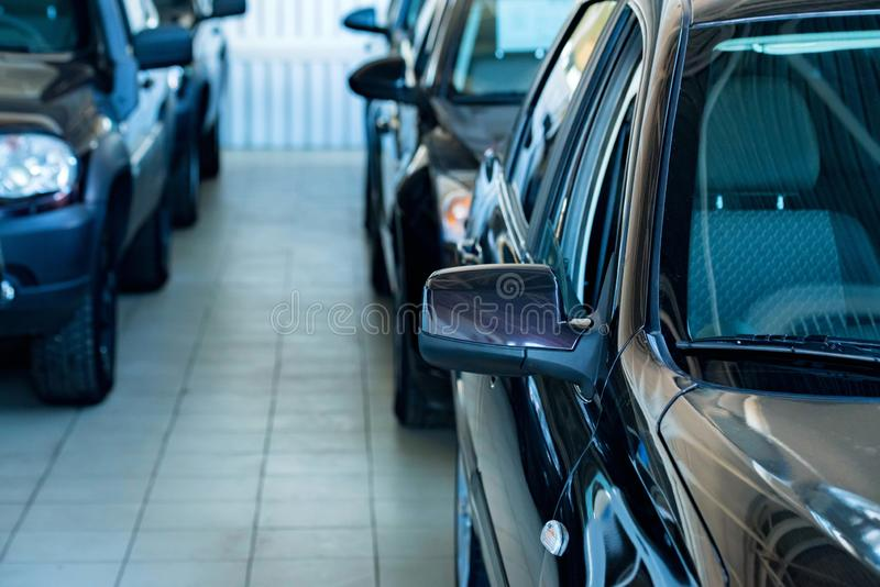 New cars at dealer showroom blurred background. Stock of cars in showroom of automobile dealer with blurred background royalty free stock photos