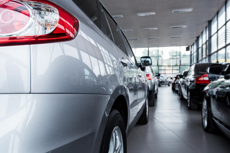 New cars at dealer showroom. Stock of cars in showroom of automobile dealer stock photography