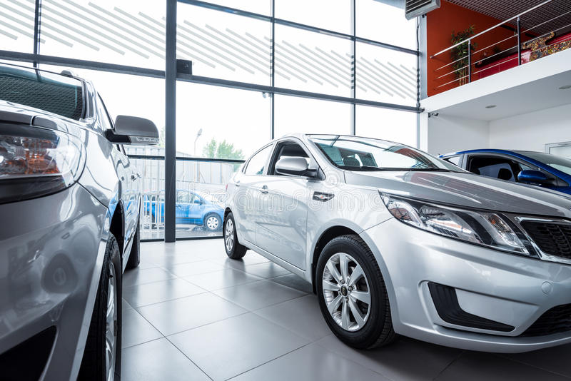 New cars at dealer showroom. Stock of cars in showroom of automobile dealer stock images