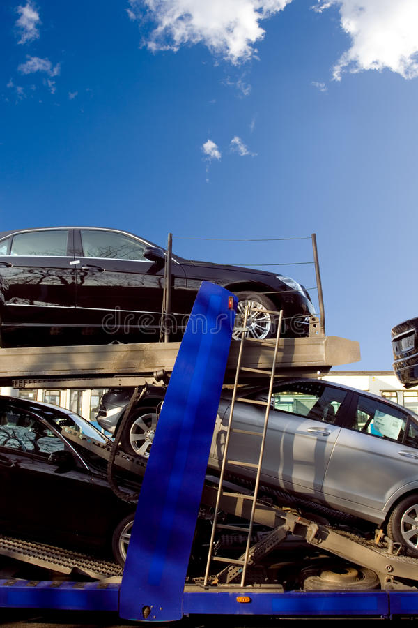 New cars going to car dealers. Car transporter full of brand new luxury cars stock image