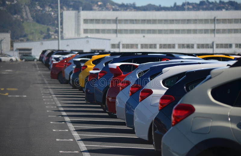 New Cars Lined Up in a Parking Lot. Brand new cars off the cargo ship awaiting shipment to dealers around the country royalty free stock photos