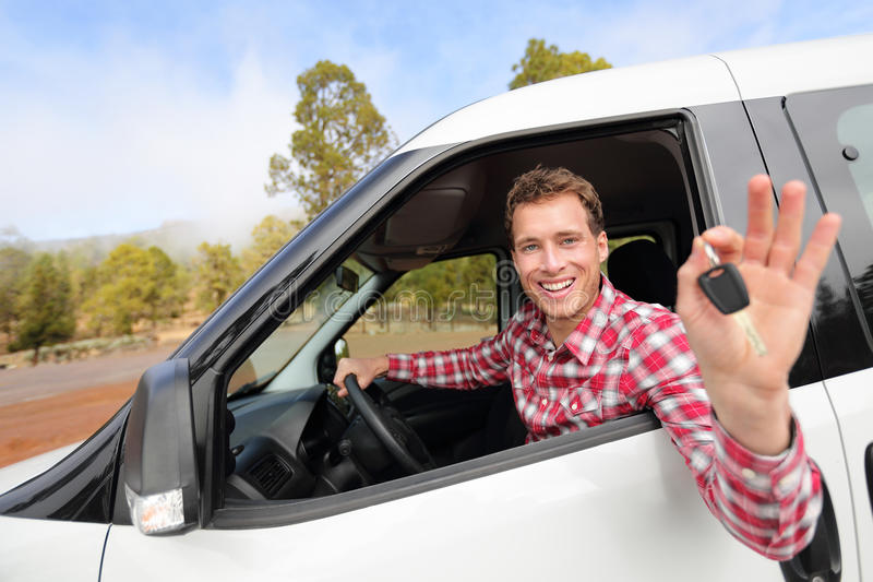 New cars - man driving car showing car keys happy. Looking at camera. Male driver on road trip in beautiful landscape nature. Focus on model royalty free stock image