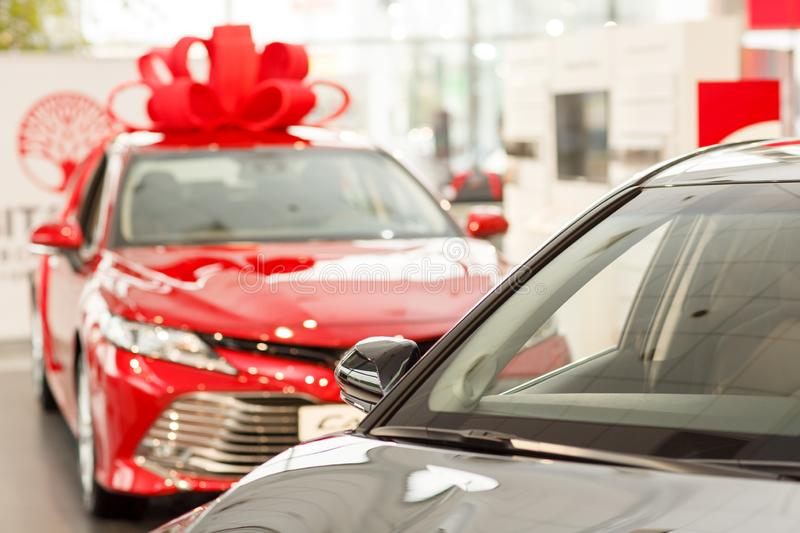 Modern cars for sale at dealership. New cars for sale at the dealership salon, copy space. Beautiful shiny red modern sedan with a big bow on the roof. Present stock photography