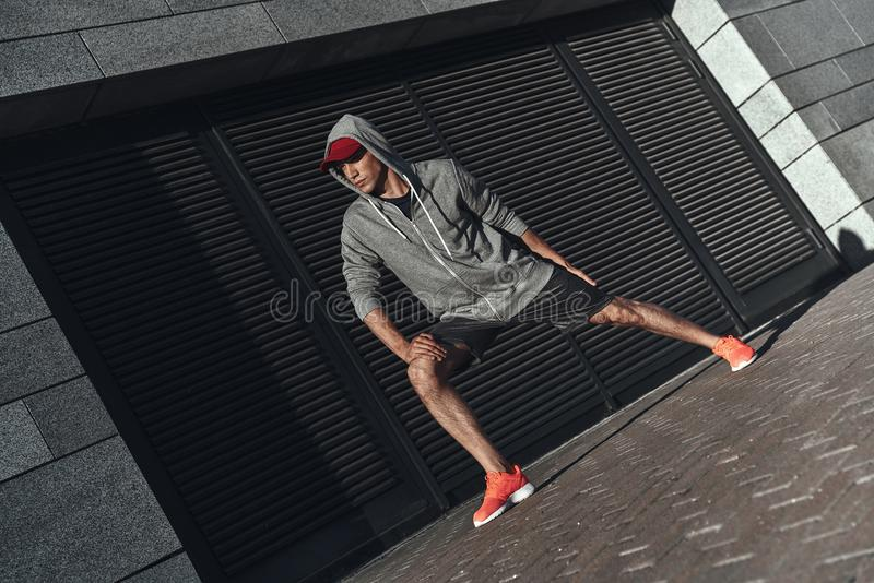 New champion. Full length of young man in sports clothing warming up while exercising outside royalty free stock images