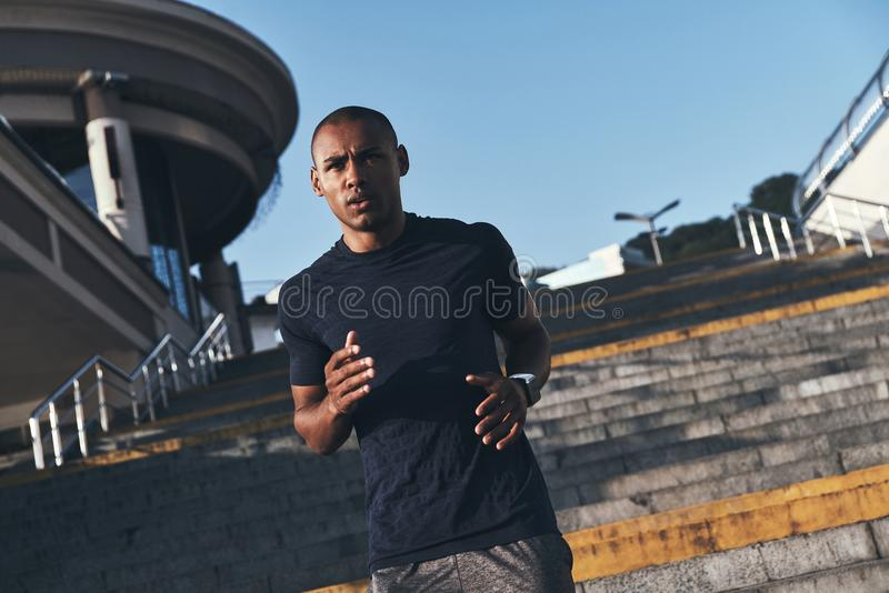 New champion. Young African man in sports clothing running down the stairs while exercising outdoors stock photos