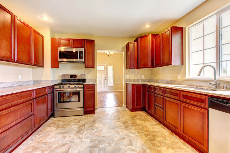 New cherry wood kitchen with stinless steal appliances. New large cherry wood kitchen with stinless steal appliances stock photography