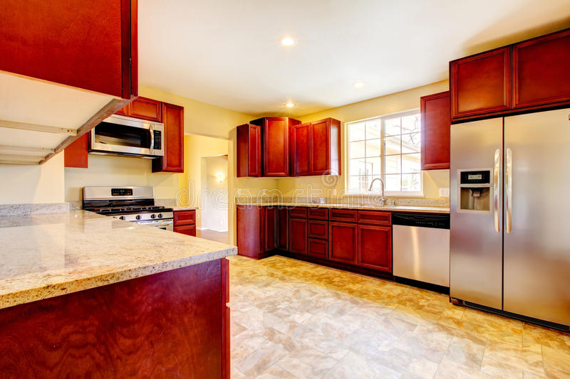 New cherry wood kitchen with stinless steal appliances. New large cherry wood kitchen with stinless steal appliances stock photo