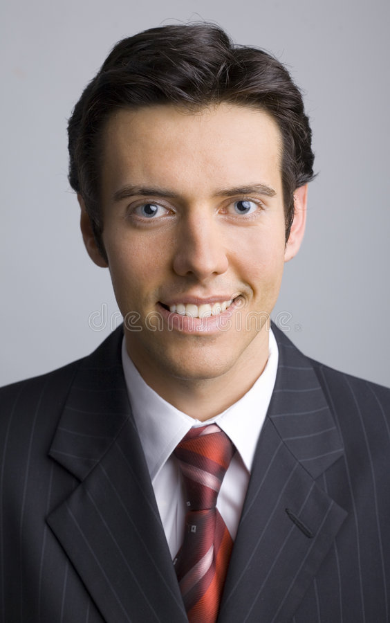 New chief. Smiling, handsome businessman. Looking at camera. Gray background, front royalty free stock photography