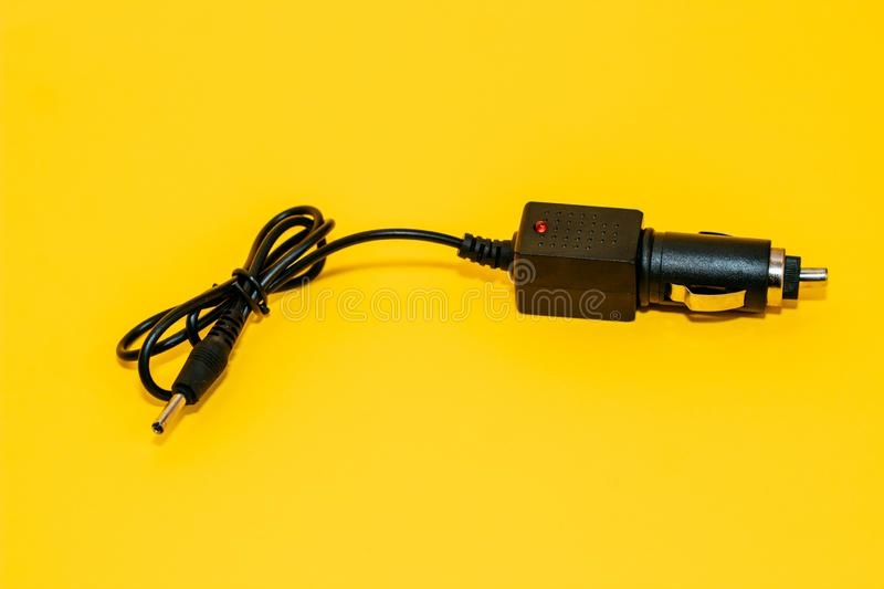 New cigarette lighter plug on yellow background royalty free stock images