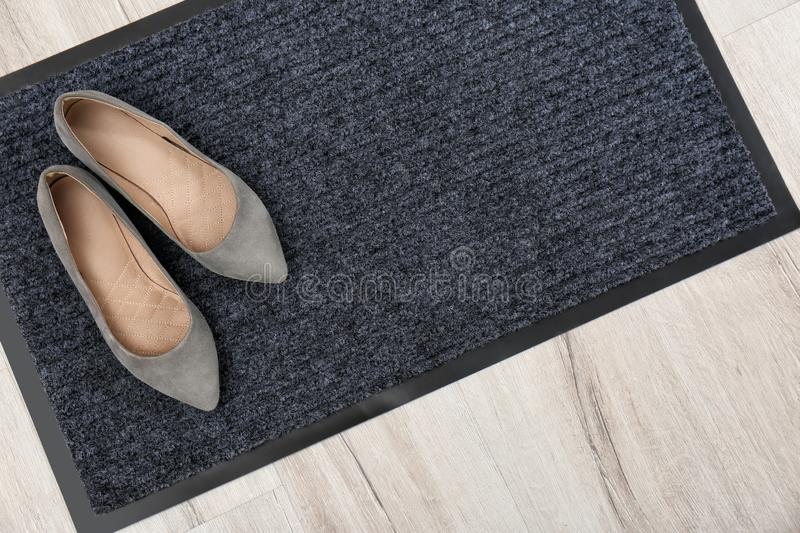 New clean doormat with shoes on floor, top view. Space for text stock images