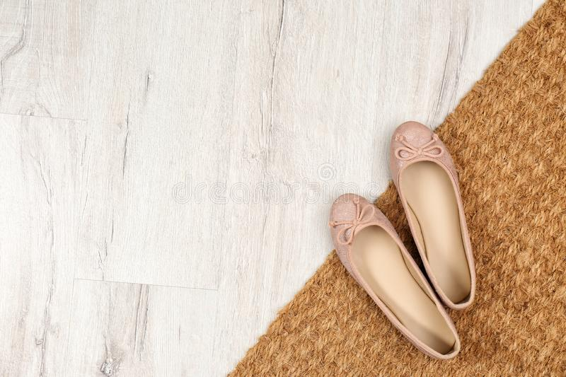 New clean doormat with shoes on floor, top view. Space for text royalty free stock photography
