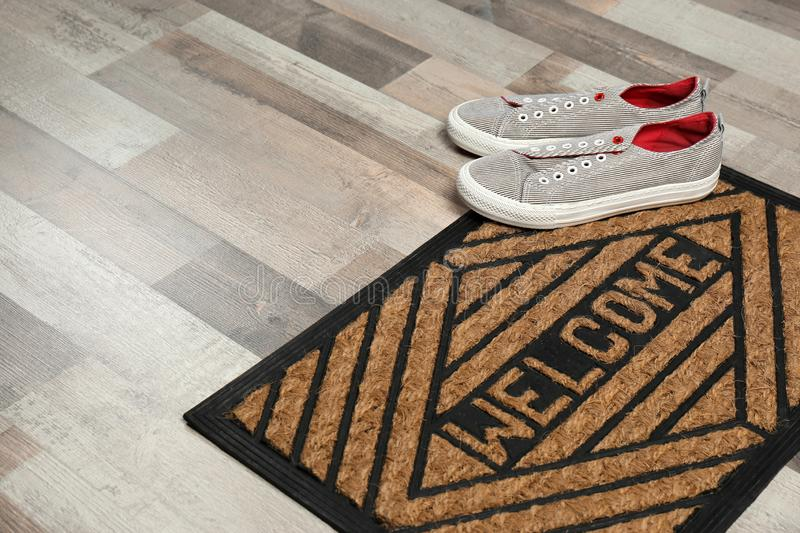 New clean doormat with word WELCOME and shoes on floor. Space for text stock photo