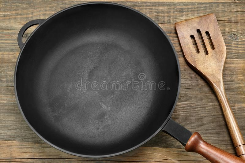 New Clean Empty Cast Iron Frying Pan And Spatula Overhead royalty free stock images